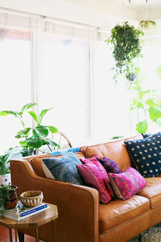 7 Items You Need to Get That Trending Bohemian Look -- We love this global boho-inspired living room with a rich cognac leather sofa, vintage batik, shibori dyed indigo and colorful kilim textile pillows in hot pink and blue patterns, tons of hanging and potted indoor plants for an urban jungle vibe, and lots of bright welcoming natural light!