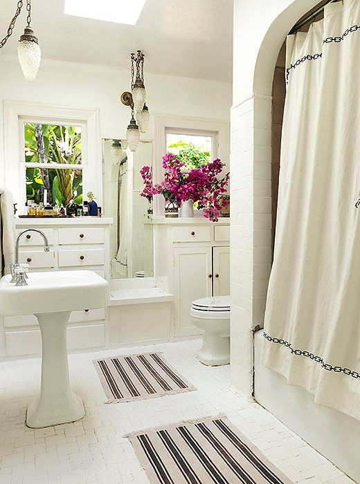 Heidi found Moroccan-style pendants to go with the matsand the embroidered shower curtain, while hot pink bougainvilleas from the garden fill a rustic pitcher to offset the all-white.