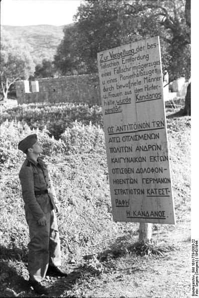 """A German soldier in front of one of the signs erected after the razing.  The text reads: 'Kandanos was destroyed in retaliation for the bestial ambush murder of a paratrooper platoon and a half-platoon of military engineers by armed men and women.'"""
