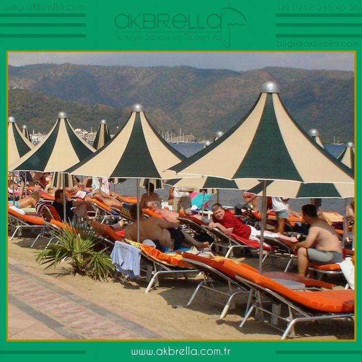 Bir plajda kullanılan bu bölümdeki renkli pagoda şemsiyeler 250 cm çapında olup şezlong üzerinde çok şık görünüyor, yeşil ve krem renkten üretilmiş bu şemsiyeler ısı ve yağmur suyunu geçirmez özellikli ithal akrilik kumaştan üretilmiştir, Akbrella web sitesinden bu ürünleri inceleyebilir online ürünleri satın alabilirsiniz.