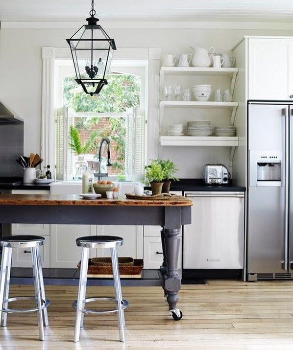 In the kitchen temper the look of metal seating and tables on casters with clean lined cabinetry and traditional lighting like designer margot austin did