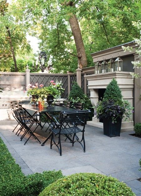 Sharon Mimran's Outdoor Dining Room. A back patio with European polish. Love the lanterns on top of the fireplace. A back patio with European polish.
