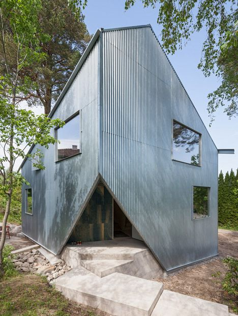 Low-cost prefabricated home clad in corrugated iron and resembles a cube with some of its corners cut off.