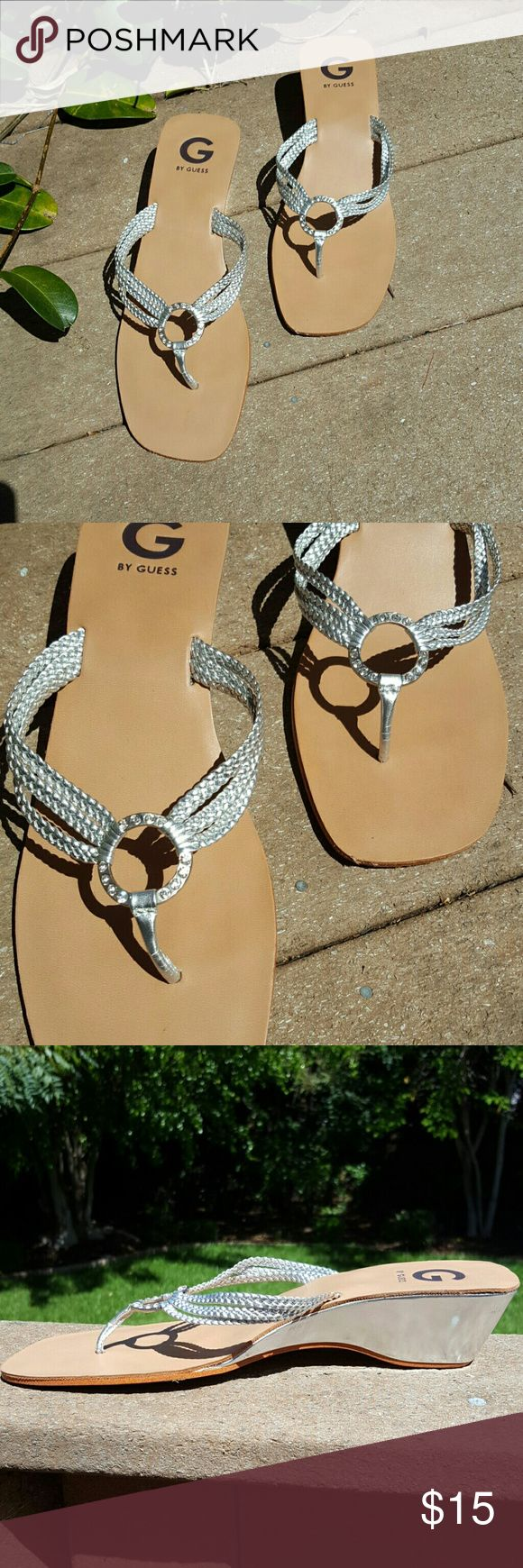 G by Guess Silver Sandals Gorgeous silver sandals by Guess. Sandals have 3 silver straps on each size of the center circle with embellishments. All embellishments are still attached. In great condition and only worn twice.   Wedge on sandals is 2 inches.   Comes from a smoke-free home. G by Guess Shoes