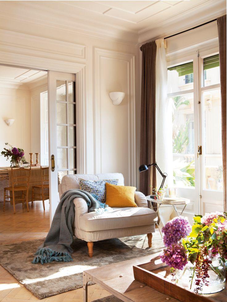 Butaca junto a balcón con cojines azul y amarillo, lámpara, velador, plaid y alfombra 00412744
