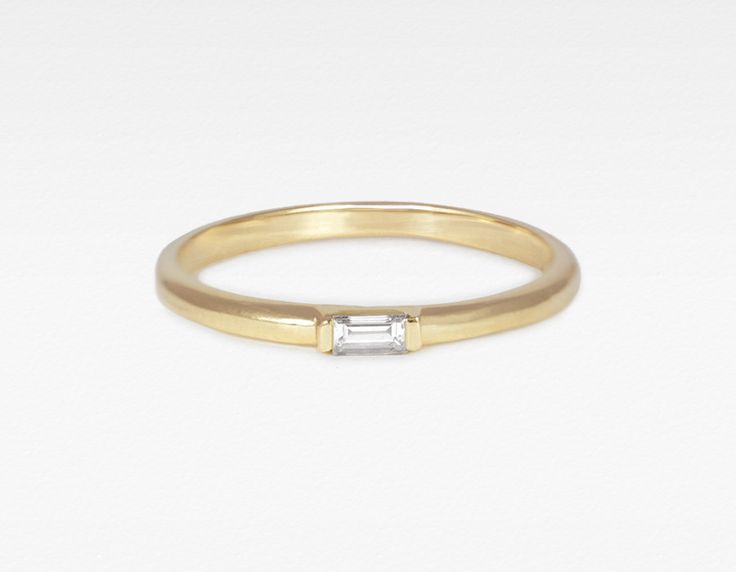 This delicate ring features a single, baguette cut diamond channel set in a 14k solid gold band.  It can be stacked with others, such as our skinny stacking rings, yet is strong enough to make a statement when worn on it's own.  Wear it either as a knuckle ring (as...