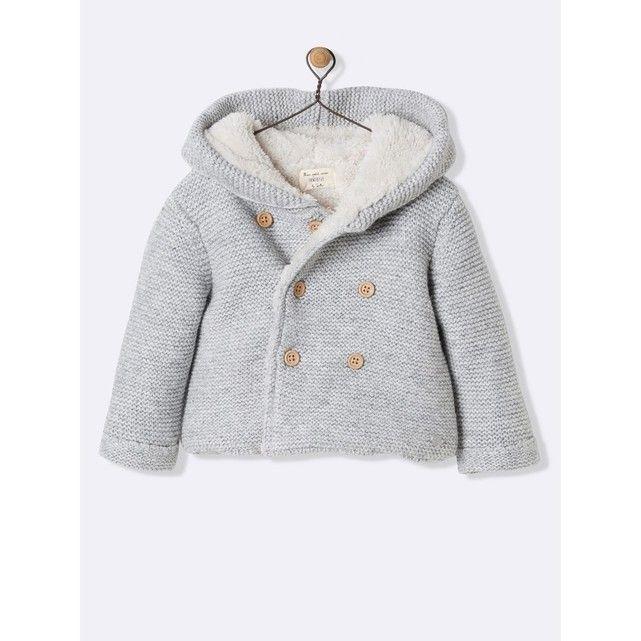 """Jeu de point mousse effet """"fait main"""" et doublure en sherpa,cette veste est un cocon de douceur et de chaleur. Nous avons mis toute notre attention et notre savoir-faire pour le confort et le bien-êtredes tout-petits. DétailsCapuche avec pompon. Petit médaillon en nacre de rivière.Ouverture double boutonnage par boutons bois.  Matière Point mousse 35% coton, 27% polyamide, 26% viscose, 7% laine, 5% angora. Doublure en sherpa 100% polyester."""