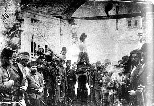 Turkish troups standing beside their hanged victim, a decapitated and mutilated body of a Greek woman in Nazilli, Aydin province. Photo: N. Rigopoulos, June 15, 1920.  www.greek-genocide.net