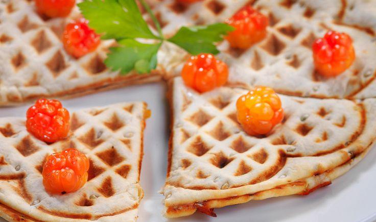 Fördela färskosten över det ena brödet. Lägg ut brieost ovanpå och klicka ut lite hjortronsylt. Toppa med persilja. Lägg på det andra brödet och tryck till lite lätt runt kanterna. Lägg brödet i det varma våffeljärnet och grädda ca 2 minuter. Dekorera med hjortron och persilja. Tips! Går också bra att grädda i smörgåsjärn eller i torr panna på spisen.