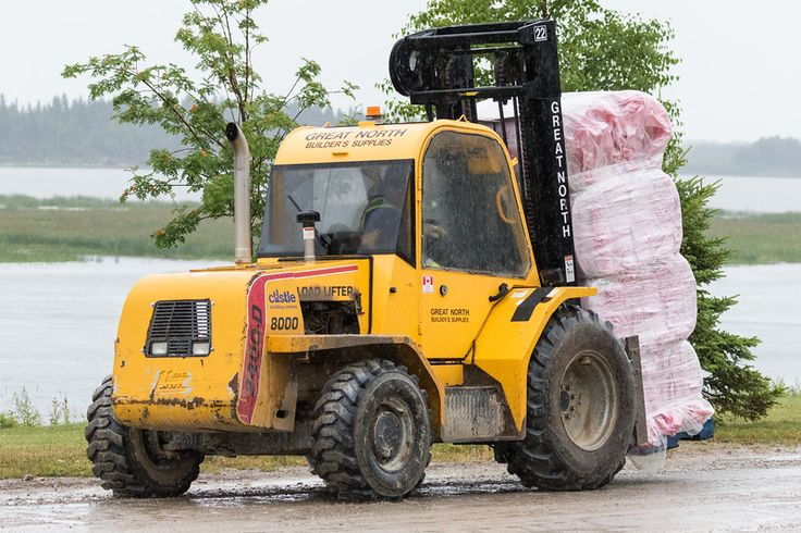 Forklift with building materials on Revillon Road in the rain.