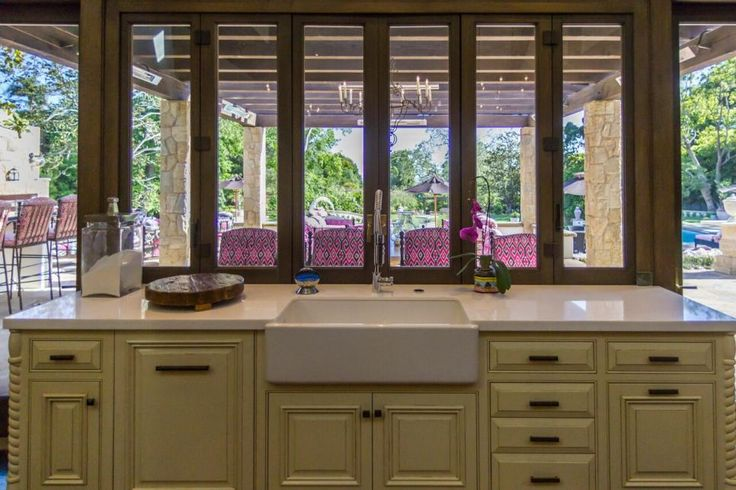 Interesting design.The connection from the kitchen to the outdoor living area is an integral part of the design. The windows above the sink bi-fold to each side and completely disappear to seamlessly connect the spaces. Cream kitchen cabinets are paired with white countertops and a farmhouse sink for a clean yet warm look.