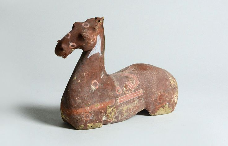 View 1: This pottery figurine is sculpted to show the strong, bold line and muscularity of the horse. Once part of an assembled set, this horse bears the characteristics associated with the famed Heavenly Horse of Fergana. Its long muscular neck, arched mane, stylistically curved snout, flared nostrils and gaping mouth depict a horse of regal origin.