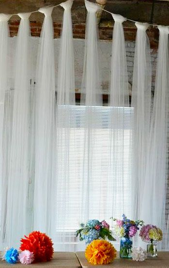 Long lengths of tulle tied around a rope for a pretty backdrop - This incorporated with string lights would make a beautiful head table backdrop
