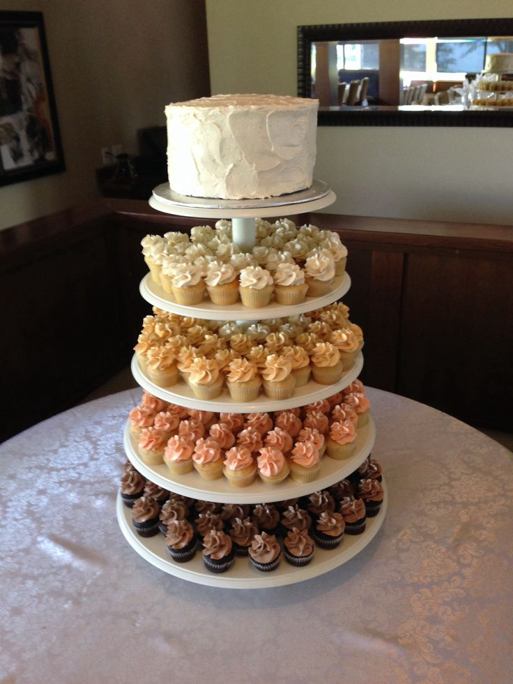 Neutral tones cupcake tower and cutting cake with stucco design