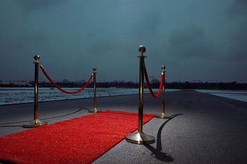 Red carpet on street, city in the background, dark clouds