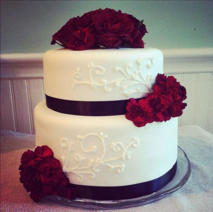 This is a 2 tier round wedding cake with fresh red roses and carnations. It has white scrolling, black ribbon and is covered in MMF.