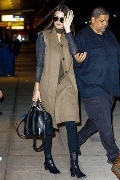 Kendall Jenner - chaleco largo sobre un top con mangas azul marino y cuerpo verde army, pantalones negros, botines negros, bolso de asa corta y gafas de sol tipo aviador.