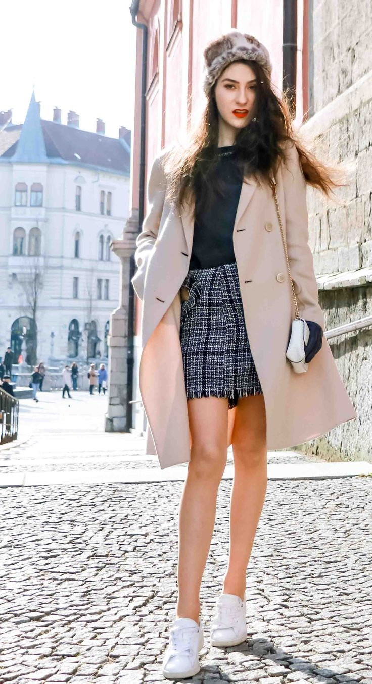 Fashion Blogger Veronika Lipar of Brunette from Wall Street dressed in white sneakers from Diesel, black and white plaid tweed mini skirt from Storets, black silk blouse from Juicy Couture, off-white double breasted wool coat from MaxMara, faux fur headband, white shoulder bag with gold chain strap, blue leather gloves on the street in Ljubljana