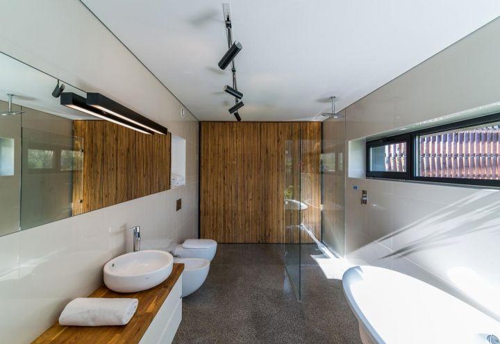 Il secondo bagno della casa su due piani disegnata da Kropka Studio nella campagna polacca è di ampie dimensioni e comprende vasca freestanding in ceramica e box doccia in vetro di Hansgrohe. Per un relax totale