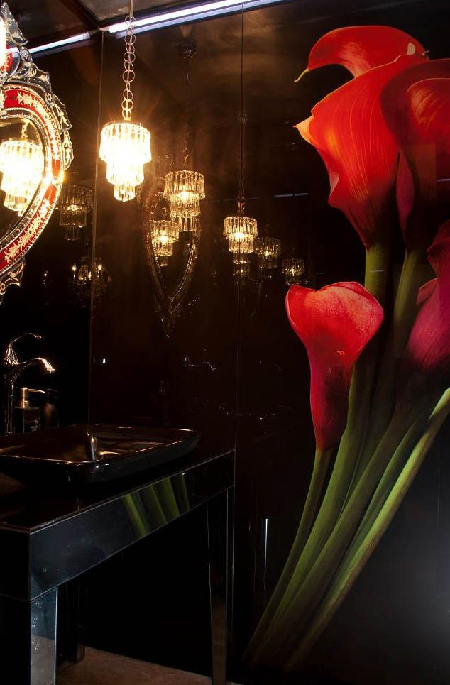 The bathroom is cladded in black and glass mirror. The client loved the idea of over scale red lilies to contrast the black walls.