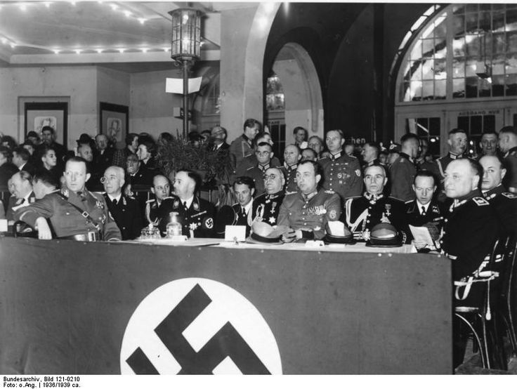 Heinrich Himmler and Berlin police chiefs Wolf Heinrich Graf von Helldorff and Kurt Daluege at a sporting event held in honor of Italian police leaders' visit to Berlin, Germany, 1936; photo 6 of 8