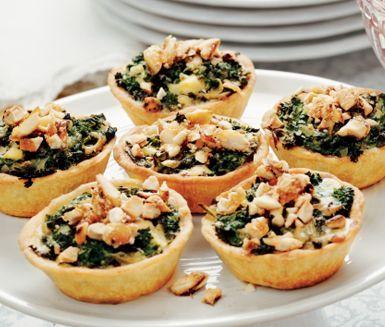 Underbara minipajer med grönkål, ädelost och mandel som passar utmärkt på julbordet. Lägg ner den goda röran av bland annat grädde, grönkål och ädelost i pajskalen och häll över äggstanningen. Strö över den honungsrostade mandeln före servering.