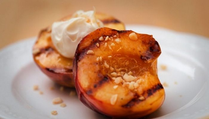 A photo of grilled peach halves with dark grill marks, lemon mascarpone and chopped almonds