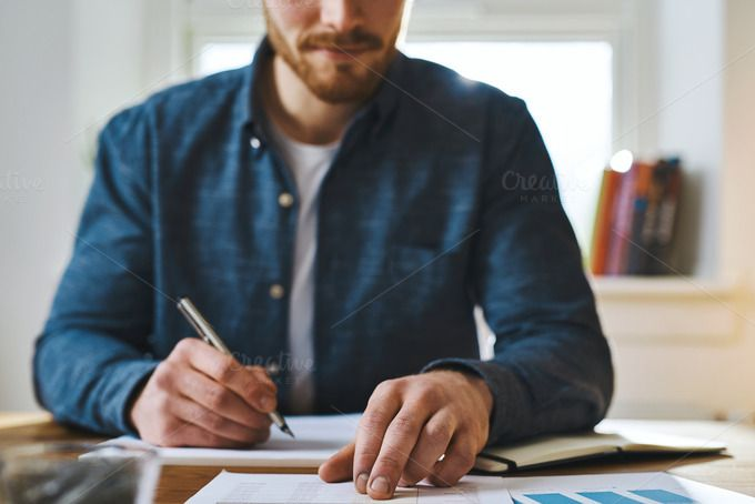 Unidentifiable man checking notes on desk by Stefan & Janni on @creativemarket