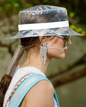 Witty touches: a model wears a perspex hat and Chanel logo earrings.