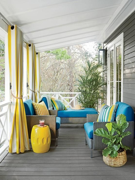 Tracery Interiors - Yellow and gray porch features a white sloped ceiling painted Benjamin Moore Cloud Cover over gray siding painted Benjamin Moore Chelsea Gray lined with gray wicker chairs and  chaise lounge accented with blue cushions placed in front of porch railings dressed in yellow stripe grommet curtains.