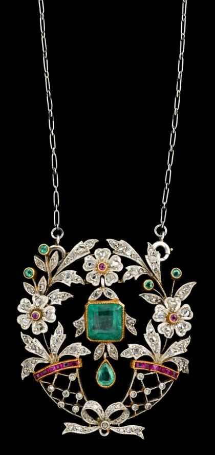 Platinum and diamond flower pendant   19th century   Delicate flower basket motif, garland of three flowers display a single drop emerald in a beaded bezel setting. Pendant displays petite rose cut diamonds, and caliber cut rubies. Accompanied by the original box.