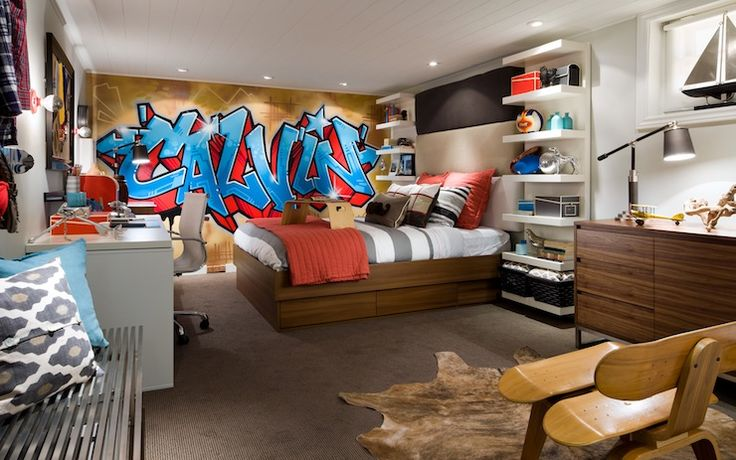 Candice Olson - boy's rooms - graffiti accent wall, graffiti wall in bedroom, taupe carpet, taupe wall to wall carpet, wall to wall carpet, wall to wall carpeting, brindle cowhide, cowhide, skateboard chair, modern skateboard chair, adjustable desk lamp, gray walls, gray wall color, mid-century dresser, modern dresser, shelves flanking headboard, built-in shelves flanking headboard, gray and white striped bedding, striped bedding, orange euro shams, orange pillow, orange coverlet, orange ...