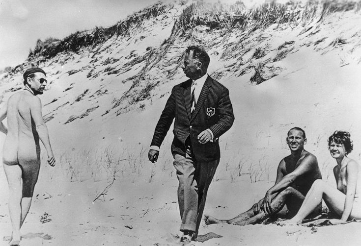 """""""Shocked By Nudity""""  """"Marzo 1959: una coppia nuda guarda divertita un uomo completamente vestito che fissa disgustato un naturista sulla spiaggia"""": didascalia originale dall'archivio Getty (BIPS/Getty Images)"""