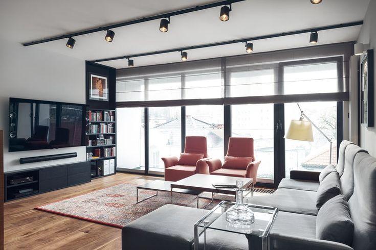 Reflektory na szynach to rozwiązanie bardzo praktyczne, bo dzięki ustawieniu odpowiedniego kąta padania światła można idealnie doświetlić każdy kąt salonu. W tym nowoczesnym wnętrzu skontrastowano je z orientalnym dywanem i eleganckimi meblami wypoczynkowymi. Przejrzyste rolety na oknach zapewniają dyskrecję, nie blokując dostępu światła.