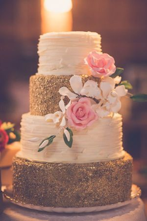 A gorgeous glittering wedding cake - we love the soft flowers and ribboned icing that off sets the gold glittering icing - Indian wedding decor ideas - wedding cake ideas #thecrimsonbride