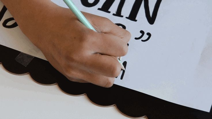 Tape the paper, graphite side down, to your chalkboard and trace over the outline of the text/design with a pencil. | Here's A Genius Trick For Making A Fancy Chalkboard Sign
