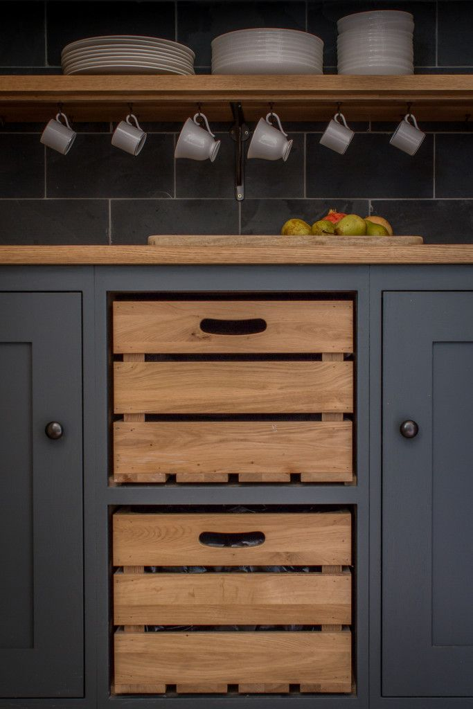 Custom made pull out drawers created using oak crates. Oak cabinets painted with Farrow & Ball Down Pipe provide a rustic contrast. Oak worktops and shelving along with slate tiles provide storage and hooks for the cups.