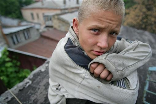 Sergei (age 15) huddles on the roof of an Odessa youth shelter. He wanted to stay at the shelter, but there were no beds available.  More children are also living or working on the streets, having been abandoned, orphaned or forced to flee domestic violence.    Ukraine, 2005 ©UNICEF/Pirozzi - http://www.unicef.org/photography