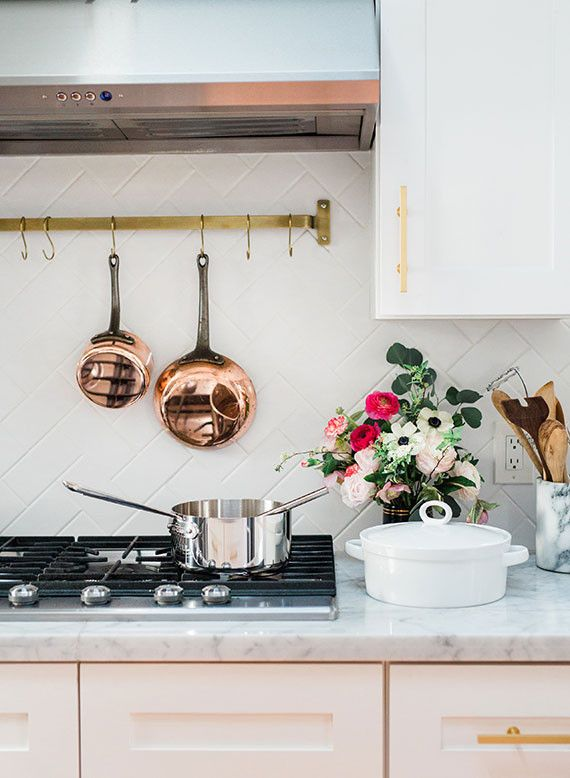 Beautiful kitchen details, including pale pink cabinets, marble countertops, herringbone backsplash and copper pots and pans | 100 Layer Cake