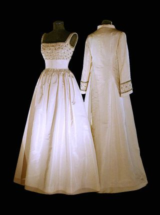 1982 - WORN BY QUEEN SILVIA OF SWEDEN TO NOBEL PRIZE CEREMONY. WHITE FAILLE WITHA BODICE PATTERNED WITH PEARLS AND CRYSTALS AND WORN WITH A MATCHING CLOAK. DESIGNED BY JORGEN BENDER, COPENHAGEN.