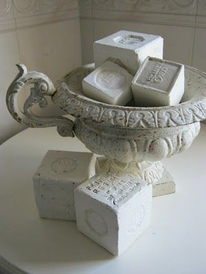 put soaps in an urn, look in garden shop outdoor planter section for inexpensive urns