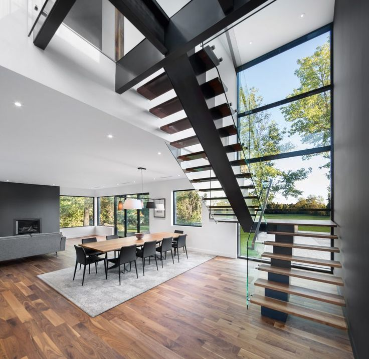 An open staircase in this house leads to a glass-floored bridge on the upper level, which connects the master bedroom to a library and guest suite.