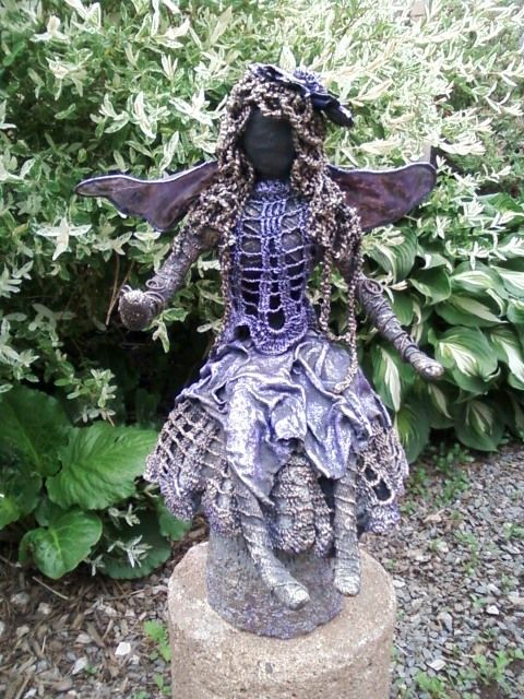This is the purple smoke fairy .. old cotton doilies make such interesting clothing and/or base covers.  The mushroom she is sitting on was made using an old aspic mold - I filled it with cement, just like making sandcastles in the sand when you were a kid.