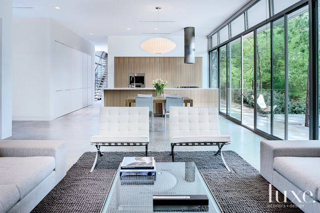 Two white-leather Barcelona chairs from Knoll frame the seating suite, while the George Nelson pendant and Bulthaup's cylindrical stove hood create an asymmetric harmony within the room. The light concrete floor, the darker rug from Ligne Roset, and then the lighter chairs creates a rhythmic contrast.