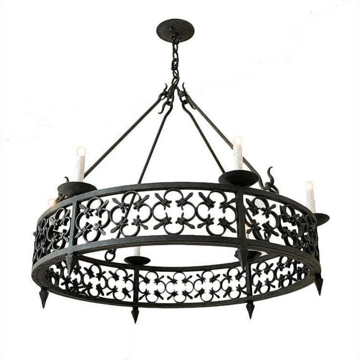 Large round wrought iron chandelier with modified fleur de lis pattern detailing from