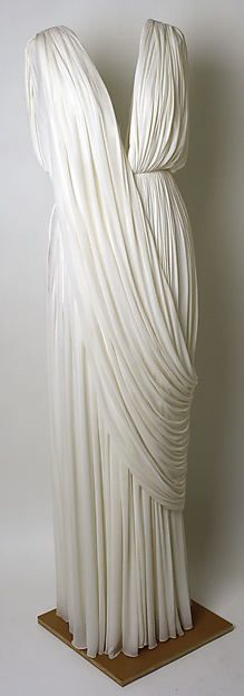 The collections of Madame Grès were prized for the pleated silk jersey gowns that ended each of her shows. With their himation-like draped swags, these designs are a relaxed version of the fine dense pleating that generally covers her fitted, highly structured bodices
