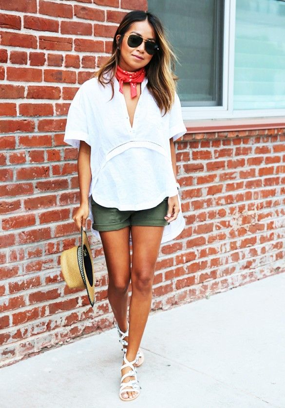 A white top is worn with green shorts, white gladiator sandals, straw hat, bandana as scarf and aviators.: