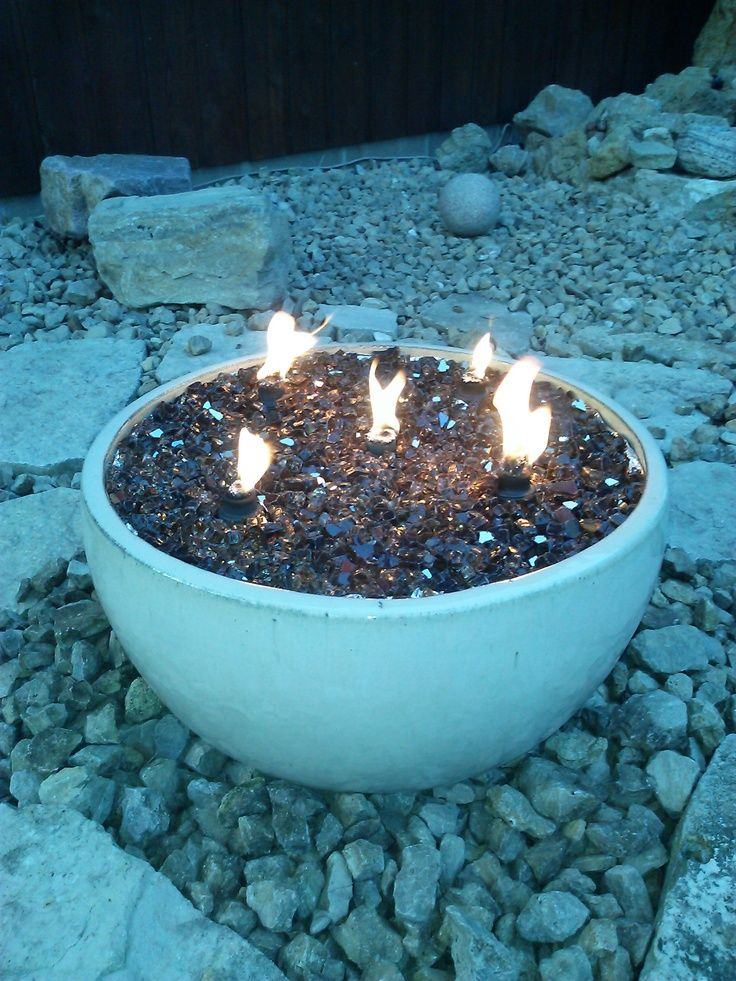 A fire pit in a pot using reflective glass pieces and small tiki torches.