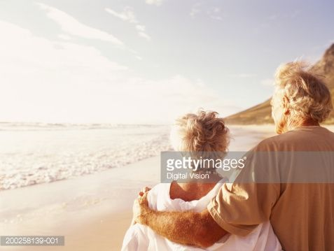 Stock Photo : Senior couple embracing on beach, rear view