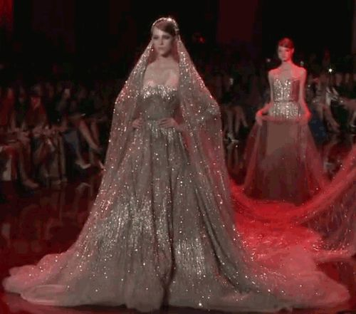 faeshion: sam-a-s: Elie Saab Haute Couture Autumn 2013 titania This wedding gown, made by Crysteal, is a work of complex magic. Actual smoke has been enchanted to act like fabric and suspend thousands of miniscule glass spheres filled with white light and charmed to twinkle alluringly. The overall effect is like looking into a galaxy.